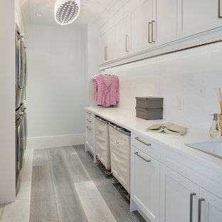 Example of a transitional galley light wood floor laundry room design in Miami with shaker cabinets, white cabinets, a stacked washer/dryer and white walls