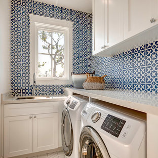 Example of a beach style l-shaped white floor dedicated laundry room design in Los Angeles with an undermount sink, shaker cabinets, white cabinets, white walls, a side-by-side washer/dryer and white countertops