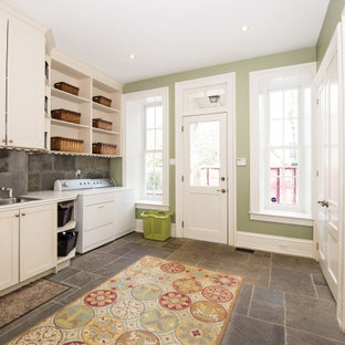Photo of a large transitional single-wall utility room in Philadelphia with a drop-in sink, shaker cabinets, white cabinets, grey splashback, green walls, a side-by-side washer and dryer, grey floor and white benchtop.