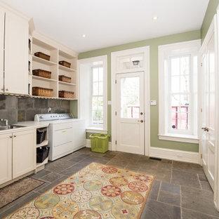 Esempio di una grande lavanderia multiuso chic con lavello da incasso, ante in stile shaker, ante bianche, paraspruzzi grigio, pareti verdi, lavatrice e asciugatrice affiancate, pavimento grigio e top bianco