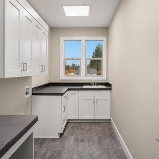 Idéer för att renovera en mellanstor vintage svarta l-formad svart tvättstuga enbart för tvätt, med en nedsänkt diskho, luckor med infälld panel, vita skåp, kaklad bänkskiva, grå väggar, vinylgolv, en tvättmaskin och torktumlare bredvid varandra och grått golv