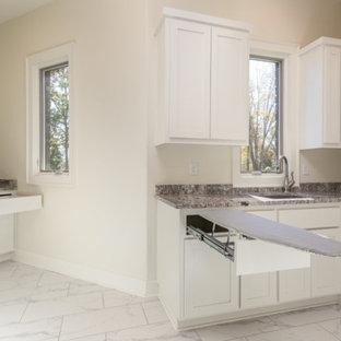 Inspiration för ett stort funkis u-format grovkök, med en undermonterad diskho, skåp i shakerstil, vita skåp, granitbänkskiva, beige väggar, marmorgolv, en tvättmaskin och torktumlare bredvid varandra och vitt golv