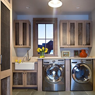 Inspiration for a rustic single-wall gray floor dedicated laundry room remodel in Denver with a farmhouse sink, medium tone wood cabinets, gray walls, beige countertops and shaker cabinets