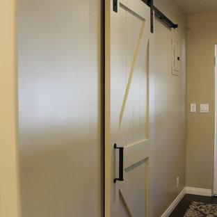 Klassisk inredning av en mellanstor parallell tvättstuga enbart för tvätt, med luckor med profilerade fronter, vita skåp, bänkskiva i kvarts, beige väggar, korkgolv, en tvättmaskin och torktumlare bredvid varandra och brunt golv