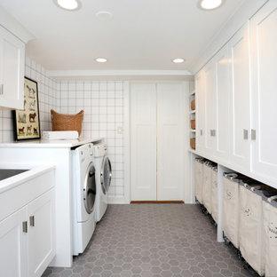Idee per una sala lavanderia tradizionale con pareti bianche, pavimento in gres porcellanato, pavimento grigio, lavello sottopiano, ante in stile shaker, ante bianche, lavatrice e asciugatrice affiancate, top bianco e carta da parati