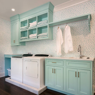 This is an example of a mid-sized traditional single-wall dedicated laundry room in Jacksonville with a drop-in sink, beaded inset cabinets, turquoise cabinets, dark hardwood floors, a side-by-side washer and dryer and white benchtop.