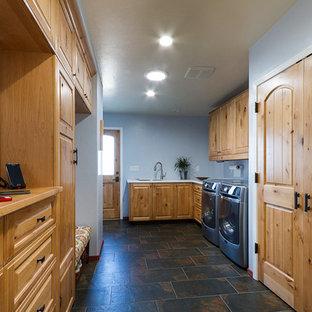 Esempio di una sala lavanderia american style con lavello sottopiano, ante con bugna sagomata, ante in legno scuro, top in legno, pareti blu, pavimento in gres porcellanato e lavatrice e asciugatrice affiancate