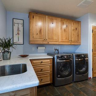 Bild på ett amerikanskt u-format grovkök, med en undermonterad diskho, luckor med upphöjd panel, skåp i mellenmörkt trä, bänkskiva i koppar, klinkergolv i porslin, en tvättmaskin och torktumlare bredvid varandra och blå väggar