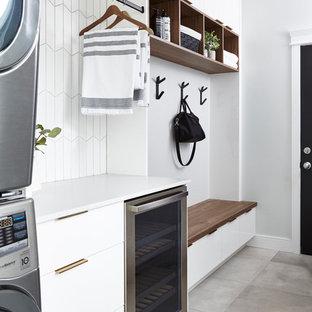 Modern inredning av ett litet vit parallellt vitt grovkök, med släta luckor, vita skåp, bänkskiva i kvarts, grå väggar, klinkergolv i porslin, en tvättpelare och grått golv