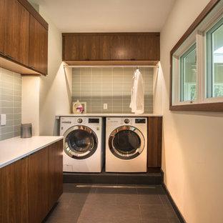 Immagine di una lavanderia moderna con ante lisce, ante in legno bruno, pareti grigie, lavatrice e asciugatrice affiancate, pavimento nero e top bianco