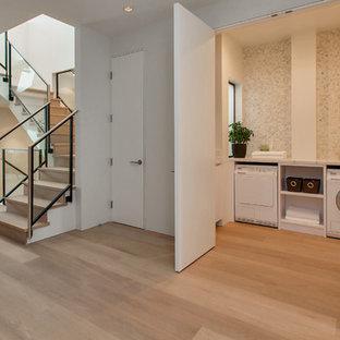 Esempio di un piccolo ripostiglio-lavanderia design con pareti beige, parquet chiaro e pavimento beige