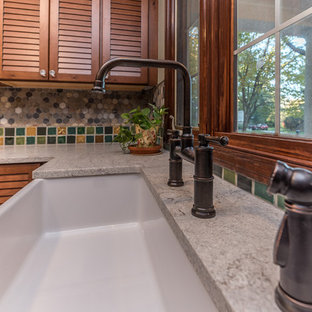 Inspiration for a large craftsman u-shaped slate floor and multicolored floor utility room remodel in Detroit with a farmhouse sink, louvered cabinets, distressed cabinets, quartz countertops, green walls, a stacked washer/dryer and gray countertops