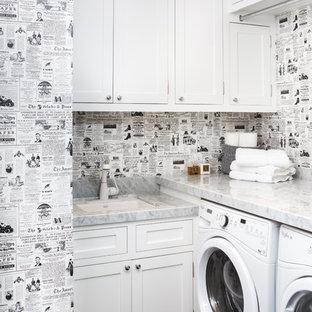 Bild på en vintage grå l-formad grått tvättstuga enbart för tvätt, med en undermonterad diskho, skåp i shakerstil, vita skåp, flerfärgade väggar och en tvättmaskin och torktumlare bredvid varandra