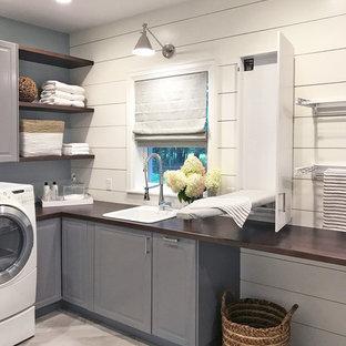 Idéer för en stor klassisk bruna tvättstuga enbart för tvätt, med luckor med upphöjd panel, grå skåp, träbänkskiva, klinkergolv i porslin, en tvättmaskin och torktumlare bredvid varandra, grått golv, en nedsänkt diskho och vita väggar