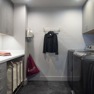 Modern inredning av ett mellanstort parallellt grovkök, med en undermonterad diskho, släta luckor, grå skåp, bänkskiva i koppar, grå väggar, betonggolv och en tvättmaskin och torktumlare bredvid varandra