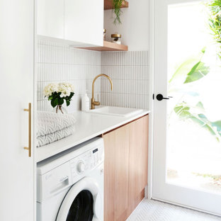This is an example of a contemporary single-wall dedicated laundry room in Gold Coast - Tweed with quartz benchtops, white benchtop, a drop-in sink, flat-panel cabinets, light wood cabinets, white walls, an integrated washer and dryer and white floor.