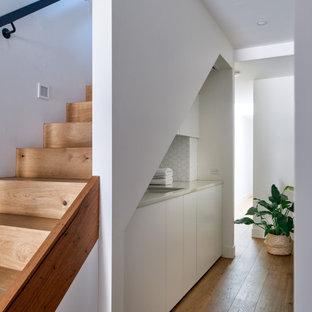 Inspiration för små moderna parallella vitt tvättstugor, med en undermonterad diskho, vita skåp, bänkskiva i kvarts, vitt stänkskydd, stänkskydd i mosaik, vita väggar, ljust trägolv, tvättmaskin och torktumlare byggt in i ett skåp och brunt golv