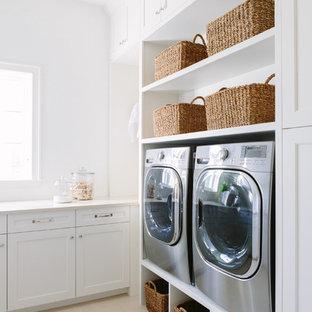 Klassisk inredning av en beige l-formad beige tvättstuga enbart för tvätt, med en undermonterad diskho, luckor med profilerade fronter, vita skåp, bänkskiva i koppar, vita väggar, klinkergolv i porslin, en tvättmaskin och torktumlare bredvid varandra och beiget golv