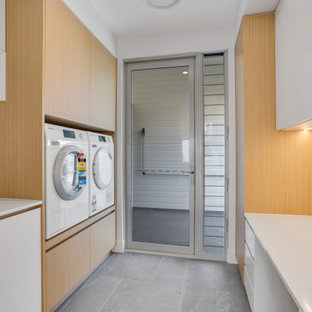 Design ideas for a mid-sized beach style galley dedicated laundry room in Brisbane with an undermount sink, brown cabinets, quartz benchtops, grey splashback, mosaic tile splashback, grey walls, porcelain floors, a stacked washer and dryer, grey floor and white benchtop.
