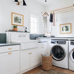 Inredning av en klassisk gröna l-formad grönt tvättstuga enbart för tvätt, med en rustik diskho, luckor med infälld panel, vita skåp, granitbänkskiva, vita väggar, ljust trägolv, en tvättmaskin och torktumlare bredvid varandra och beiget golv