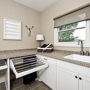 Large arts and crafts slate floor laundry room photo in Grand Rapids with a drop-in sink, recessed-panel cabinets, white cabinets, limestone countertops and beige walls