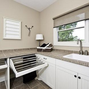 Inspiration för en stor amerikansk tvättstuga, med en nedsänkt diskho, luckor med infälld panel, vita skåp, bänkskiva i kalksten, beige väggar och skiffergolv