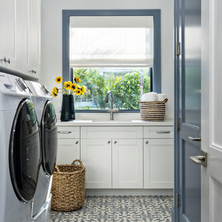 Beach style multicolored floor dedicated laundry room photo in Miami with an undermount sink, shaker cabinets, white cabinets, white walls, a side-by-side washer/dryer and white countertops