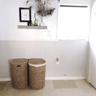 Foto på ett mellanstort 60 tals vit linjärt grovkök, med släta luckor, vita skåp, träbänkskiva, lila väggar, vinylgolv, en tvättmaskin och torktumlare bredvid varandra och beiget golv