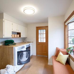 Foto på ett mellanstort vintage beige linjärt grovkök, med en undermonterad diskho, skåp i shakerstil, vita skåp, träbänkskiva, vita väggar, korkgolv, en tvättmaskin och torktumlare bredvid varandra och brunt golv