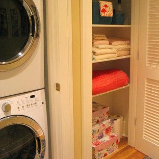 Immagine di un ripostiglio-lavanderia tradizionale di medie dimensioni con ante a persiana, ante bianche, pareti gialle, pavimento in legno massello medio, lavatrice e asciugatrice a colonna e pavimento marrone