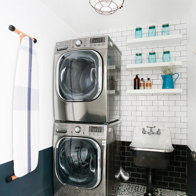 Transitional multicolored floor dedicated laundry room photo in Los Angeles with open cabinets, white cabinets, multicolored walls and a stacked washer/dryer