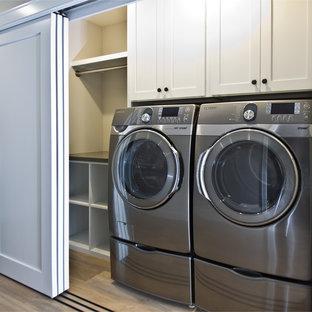 Idee per un piccolo ripostiglio-lavanderia chic con ante in stile shaker, ante bianche, pareti bianche, parquet chiaro e lavatrice e asciugatrice affiancate