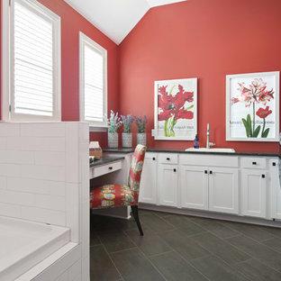 インディアナポリスのトランジショナルスタイルのおしゃれなランドリールーム (ドロップインシンク、シェーカースタイル扉のキャビネット、黄色いキャビネット、赤い壁、グレーの床、黒いキッチンカウンター) の写真