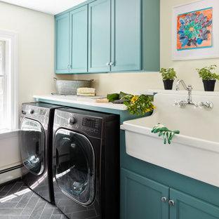 Cette image montre une buanderie traditionnelle avec un évier de ferme, un placard avec porte à panneau encastré, des portes de placard turquoises, un mur beige, des machines côte à côte, un sol gris et un plan de travail blanc.