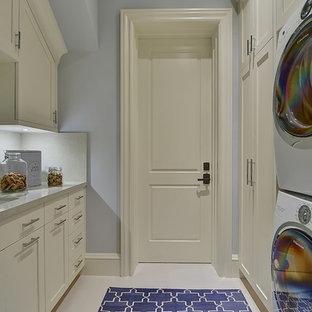 Immagine di un'ampia lavanderia chic con lavello da incasso, ante in stile shaker, top in quarzite, pavimento in gres porcellanato, lavatrice e asciugatrice a colonna, ante bianche e pareti grigie