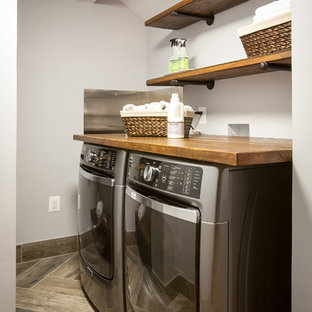Example of a small mountain style l-shaped porcelain floor and brown floor utility room design in DC Metro with wood countertops, gray walls and a side-by-side washer/dryer