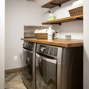 Bild på ett litet rustikt l-format grovkök, med träbänkskiva, grå väggar, klinkergolv i porslin, en tvättmaskin och torktumlare bredvid varandra och brunt golv