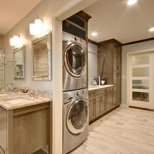 Immagine di un'ampia lavanderia multiuso classica con lavello sottopiano, ante con riquadro incassato, ante grigie, top in onice, pavimento con piastrelle in ceramica, lavatrice e asciugatrice a colonna, pavimento grigio e pareti grigie
