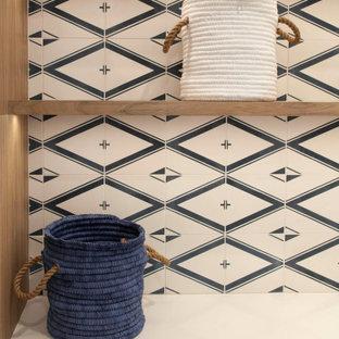 Foto på en liten maritim vita l-formad tvättstuga enbart för tvätt, med en undermonterad diskho, släta luckor, skåp i ljust trä, bänkskiva i kvarts, blått stänkskydd, stänkskydd i cementkakel, vita väggar, klinkergolv i porslin, en tvättpelare och beiget golv