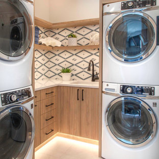 Small beach style l-shaped porcelain tile and beige floor dedicated laundry room photo in San Diego with an undermount sink, flat-panel cabinets, light wood cabinets, quartz countertops, blue backsplash, cement tile backsplash, white walls, a stacked washer/dryer and white countertops