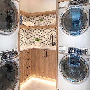 Bild på en liten maritim vita l-formad vitt tvättstuga enbart för tvätt, med en undermonterad diskho, släta luckor, skåp i ljust trä, bänkskiva i kvarts, blått stänkskydd, stänkskydd i cementkakel, vita väggar, klinkergolv i porslin, en tvättpelare och beiget golv