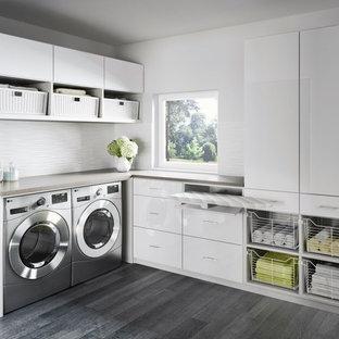 Idéer för stora funkis l-formade tvättstugor enbart för tvätt, med en tvättmaskin och torktumlare bredvid varandra, släta luckor, vita skåp, bänkskiva i kvarts, vita väggar, vinylgolv och grått golv