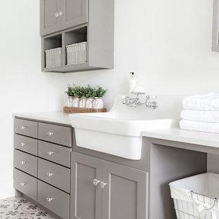 Exempel på en mellanstor lantlig vita parallell vitt tvättstuga enbart för tvätt, med en rustik diskho, skåp i shakerstil, grå skåp, bänkskiva i kvarts, vita väggar, klinkergolv i porslin och grått golv