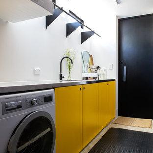 オークランドのコンテンポラリースタイルのおしゃれな洗濯室 (I型、アンダーカウンターシンク、フラットパネル扉のキャビネット、黄色いキャビネット、白い壁、コンクリートの床、上下配置の洗濯機・乾燥機、グレーの床、グレーのキッチンカウンター) の写真