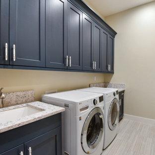 Inspiration för stora klassiska linjära blått tvättstugor enbart för tvätt, med en integrerad diskho, släta luckor, blå skåp, träbänkskiva, beige väggar, klinkergolv i keramik, en tvättmaskin och torktumlare bredvid varandra och beiget golv