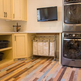 Exempel på en stor amerikansk l-formad tvättstuga enbart för tvätt, med en undermonterad diskho, luckor med upphöjd panel, gula skåp, bänkskiva i kvarts, beige väggar, en tvättpelare och målat trägolv