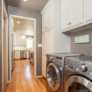 Example of a large transitional l-shaped light wood floor laundry room design in Los Angeles with an undermount sink, shaker cabinets, white cabinets, quartzite countertops, gray walls and a side-by-side washer/dryer