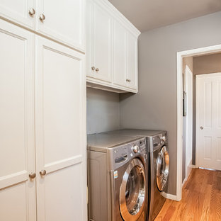 Inspiration for a large transitional l-shaped light wood floor laundry room remodel in Los Angeles with an undermount sink, shaker cabinets, white cabinets, quartzite countertops, gray walls and a side-by-side washer/dryer