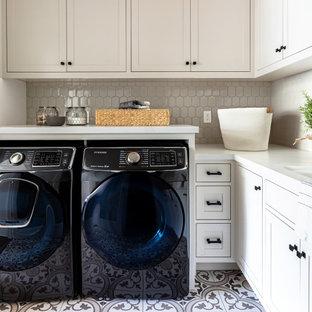 Immagine di una lavanderia multiuso country di medie dimensioni con lavello sottopiano, ante in stile shaker, ante beige, lavatrice e asciugatrice affiancate, top bianco, top in quarzo composito, pavimento con piastrelle in ceramica e pavimento multicolore
