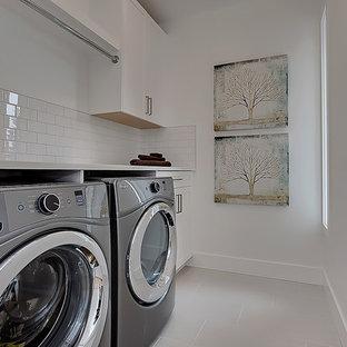 Ispirazione per una sala lavanderia scandinava con ante in stile shaker, ante bianche, pareti bianche e lavatrice e asciugatrice affiancate